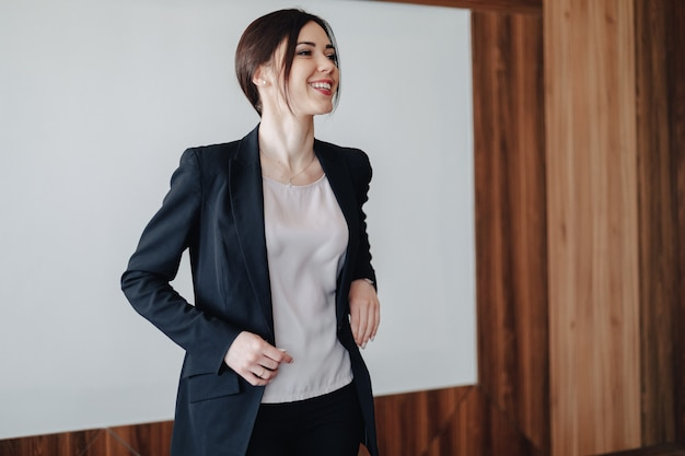 Young attractive emotional girl in business-style clothes on a plain white background in an office or audience