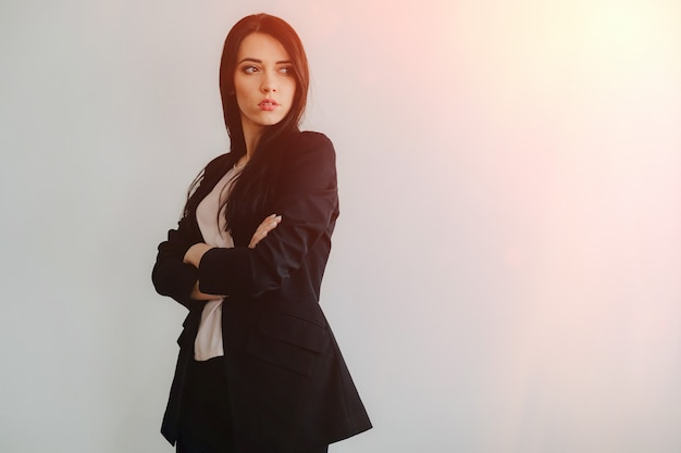 Young attractive emotional girl in business-style clothes on a plain white surface in an office or audience