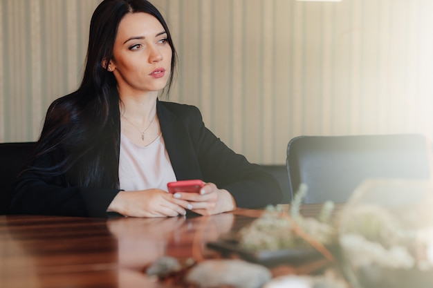 Young attractive emotional girl in business style clothes sitting at desk with phone in office or audience