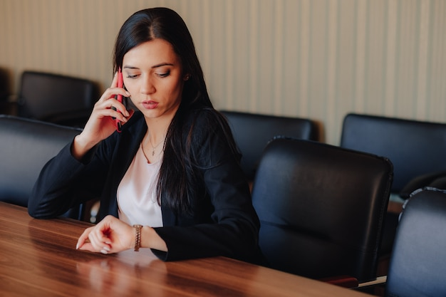 Young attractive emotional girl in business style clothes sitting at desk with phone