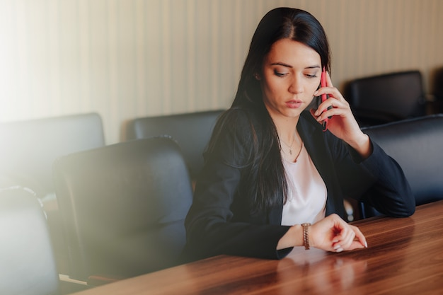 Young attractive emotional girl in business style clothes sitting at desk