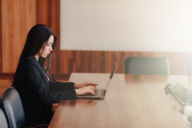 Young attractive emotional girl in business-style clothes sitting at a desk