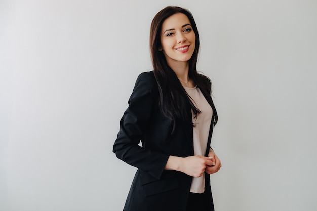 Young attractive emotional girl in business-style clothes