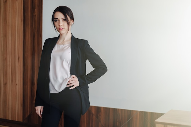 Young attractive emotional girl in businessstyle clothes o