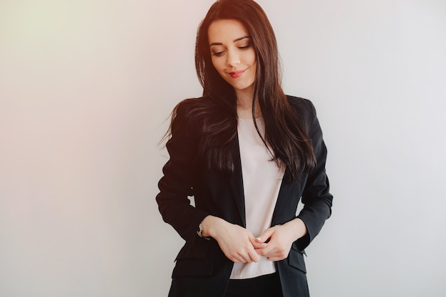 Young attractive emotional girl in businessstyle clothes