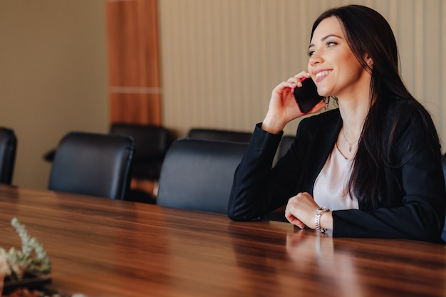 Young attractive emotional woman in business style clothing sitting at desk with phone