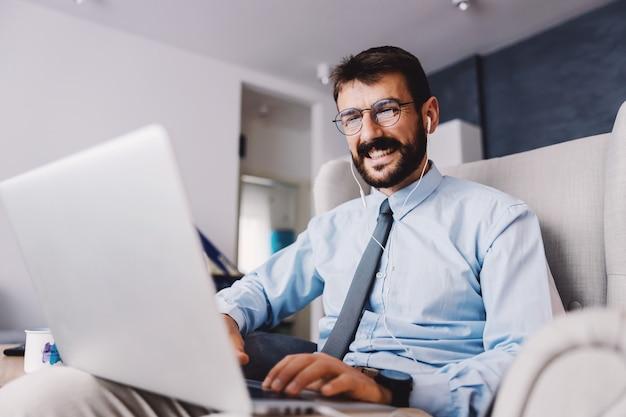 Молодой привлекательный сотрудник сидит дома и работает на ноутбуке во время вспышки вируса короны.
