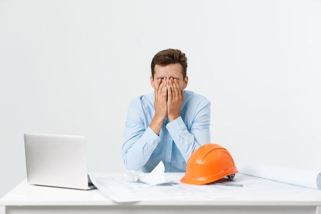 職場で疲れを感じている若い魅力的なエンジニアの男。
