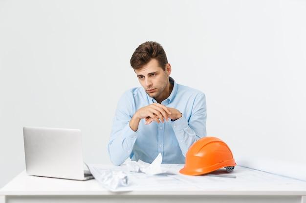 Giovane uomo attraente dell'ingegnere che si sente stanco sul posto di lavoro.
