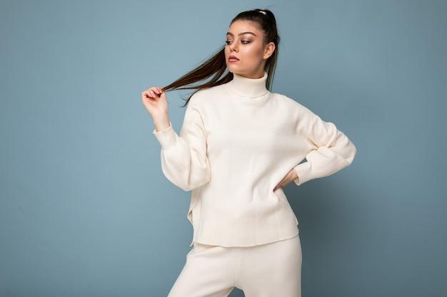 青の上に分離された白いセーターを着ている若い魅力的なヨーロッパのファッションの女性