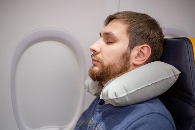 Молодой привлекательный европейский мужчина 30 лет с бородой спит, отдыхает с помощью надувной подушки для шеи в самолете. комфорт, стресс в самолете, транспорт, путешествия. запасное фото.
