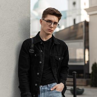 街の壁の近くにバックパックを置いて、眼鏡をかけたファッショナブルなデニムの服を着た魅力的な若いヨーロッパ人男性。ジーンズを着たハンサムな男が屋外でポーズをとる。メンズの春コレクション服。