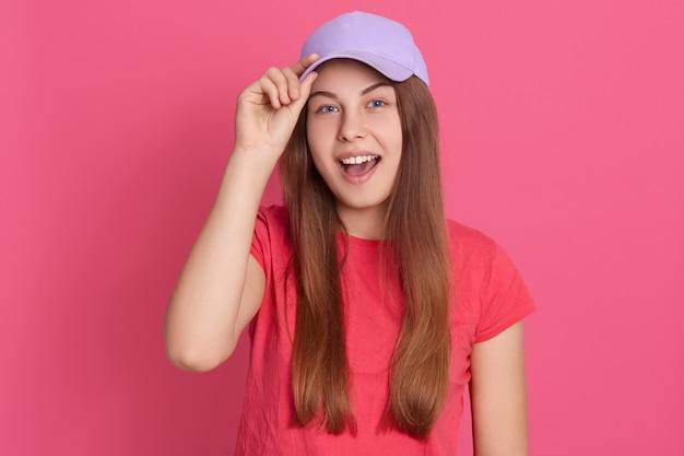 젊은 매력적인 흥분 여성 캐주얼 의류와 야구 모자를 쓰고, 모자 바이저를 만지고, 뭔가 소리 지르고, 행복해 보입니다.