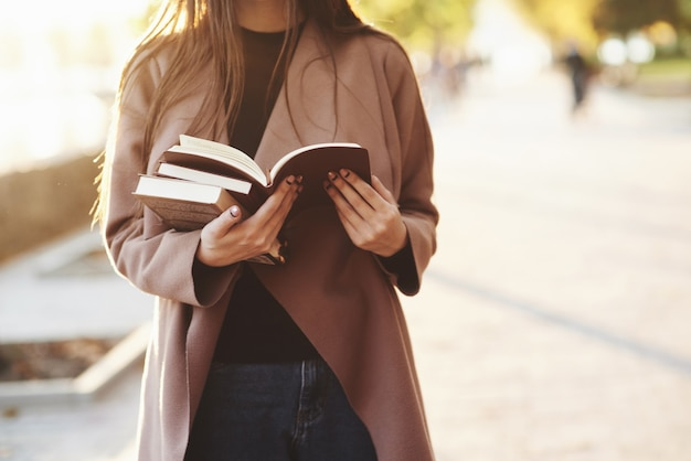 Young attractive faceless brunette girl holding a small stack of books and reading a brown one, while standing in autumn park with trees at the blurry background with a copy space.