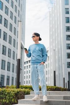 젊은 매력적인 패션 사업가 스마트폰 배경 대도시 흰색 비즈니스 센터 독서 ...