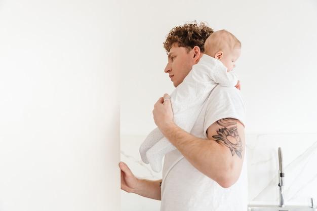 Молодой привлекательный отец смотрит в холодильник, держа своего маленького сына на кухне дома