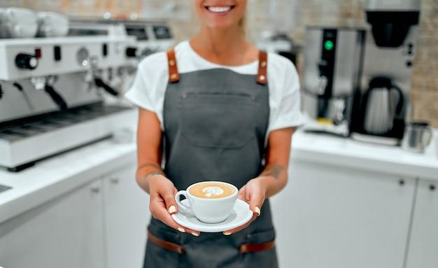 젊은 매력적인 여성 바리스타가 커피숍의 카운터에 서서 고객에게 준비된 커피 한 잔을 제공하며 미소를 짓고 있습니다.