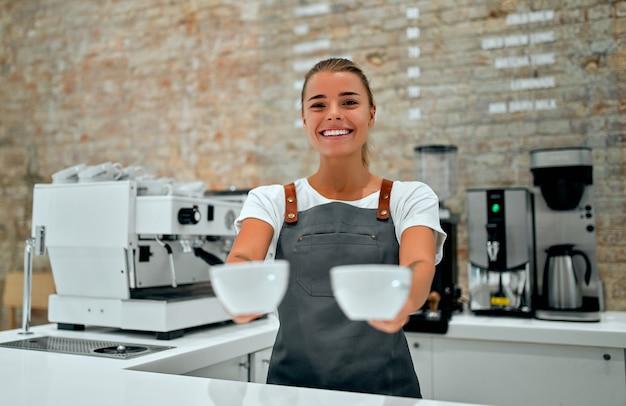若い魅力的な女性バリスタが喫茶店のカウンターに立ち、笑顔で淹れたてのコーヒーをお客様に提供しています。
