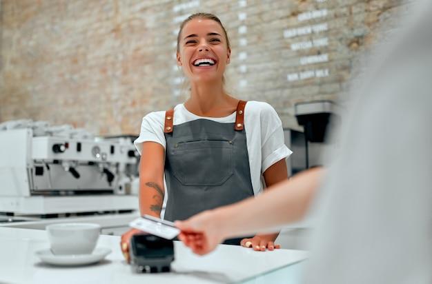 젊은 매력적인 여성 바리스타가 커피숍의 카운터에 서 있습니다. 카페에서 신용 카드로 주문 비용을 지불하는 고객.