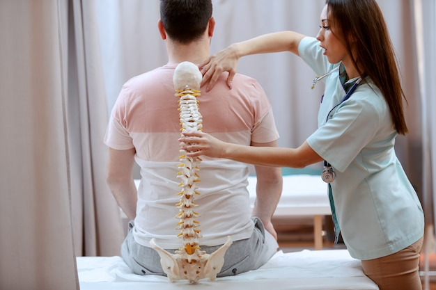 Young attractive female doctor holding spine model and truing to realize where is patient's painful place.