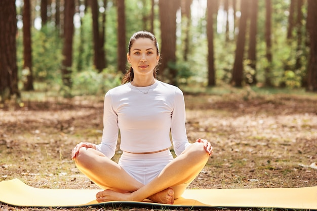 Young attractive female dresses stylish sportswear sitting with crossed legs on karemat,  keeps hands on knee, practicing yoga in forest.