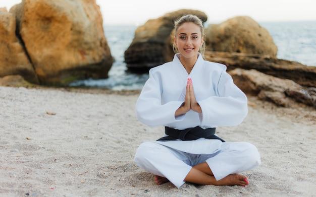 Молодой привлекательный женский боец в белом кимоно с черным поясом медитирует на диком пляже с камнями