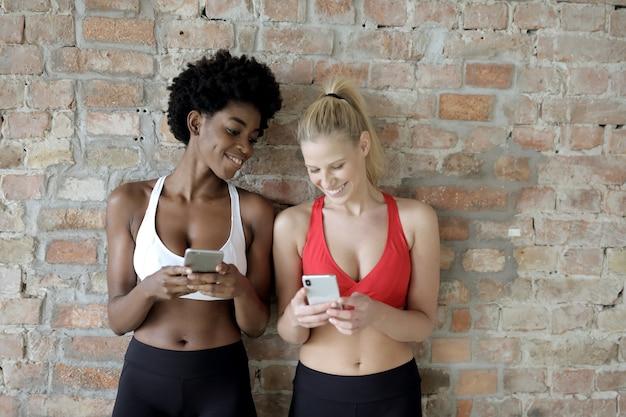 Giovani amiche attraenti che texting sul telefono e sorridente che si leva in piedi contro un muro di mattoni