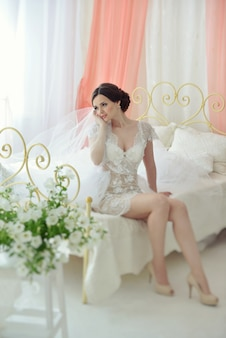 Young attractive female model girl before the wedding sitting on the bed.
