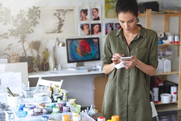 Giovane pittore femminile attraente che indossa camicia casual, in piedi nel suo laboratorio, guardando attentamente nel suo smartphone