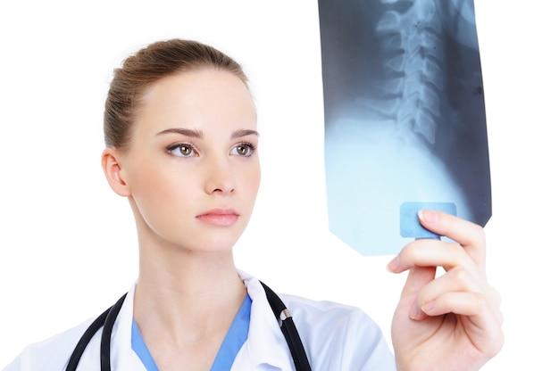Молодая привлекательная женщина-практик, глядя на рентгеновский снимок