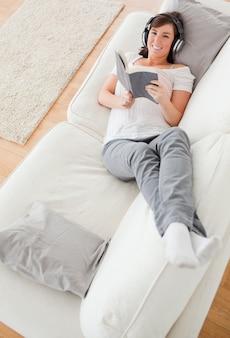 若い、魅力的、女性、横に、読書、ソファ、横たわる
