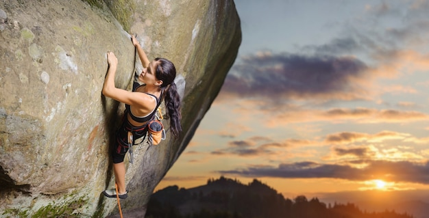 Young attractive female rock climber climbing challenging route on steep rock wall