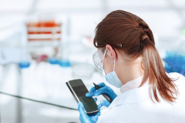 Молодая привлекательная женщина-ученый использует смартфон в лаборатории