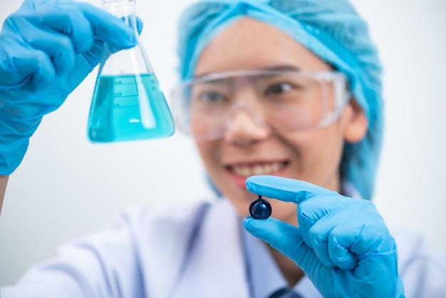 Young attractive female scientist with protective eyeglasses and mask holding a transparent pill