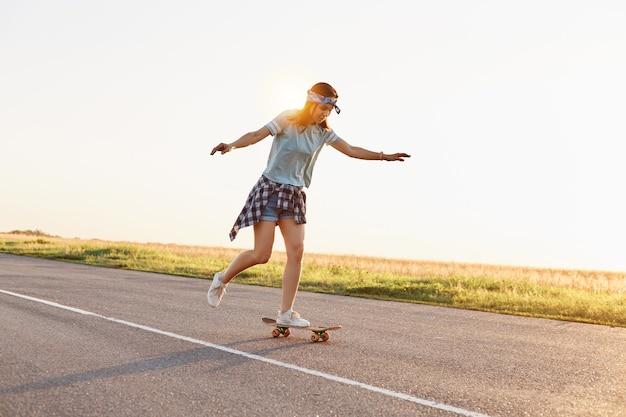 Giovane pattinatrice attraente che guida all'aperto su strada asfaltata, alzò le braccia, donna sportiva che indossa abbigliamento casual che fa skateboard da sola al tramonto in estate.