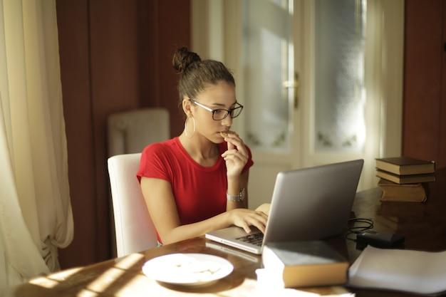 Giovane studentessa attraente che mangia i biscotti e lavora con un computer portatile