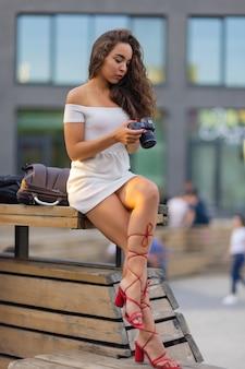 Молодая привлекательная студентка или туристка с помощью беззеркальной камеры во время прогулки по летнему городу ...