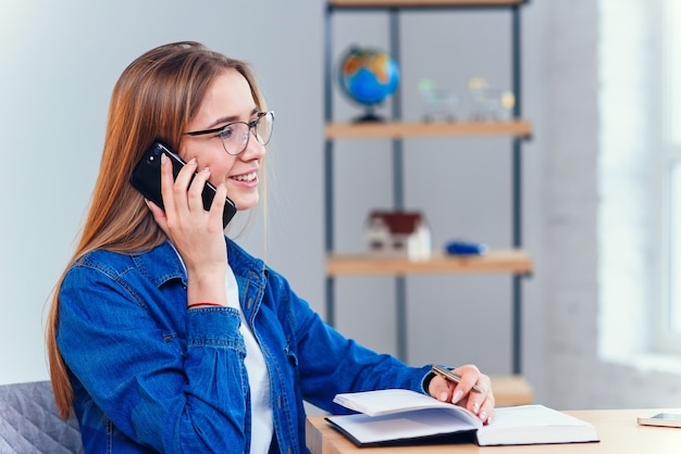 Young attractive female student uses smartphone while studying at home.