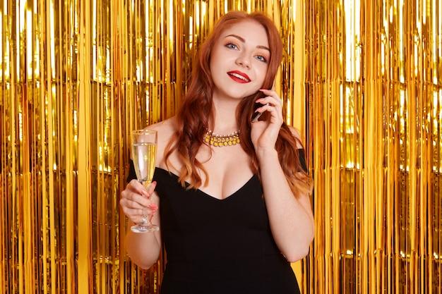 Молодая привлекательная женщина защищает черное элегантное платье и ожерелье, стоящее на золотой стене с мишурой, держа в руке бокал вина или шампанского.