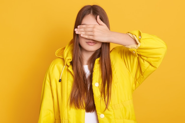 Young attractive female wearing jacket covering her eyes with hands, woman with long hair, standing against yellow wall, lady hides from her friend.