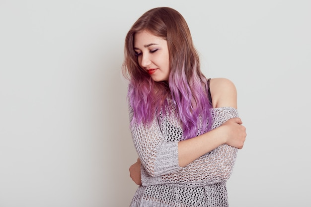 Young attractive female with lilac hair hugging herself and looking away