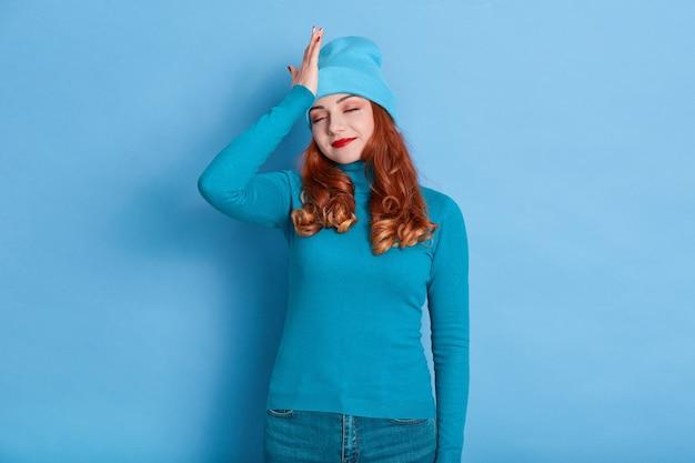 キャップと暖かいセーターで青い背景にポーズをとって、手のひらで彼女の額に触れて、赤い髪の若い魅力的な女性