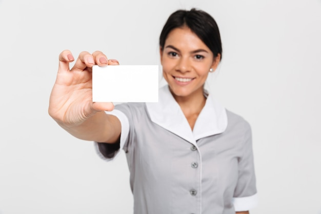 Молодая привлекательная домохозяйка в форме показа пустой визитки, выборочный фокус на карточке