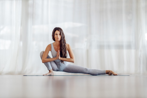 Young attractive fit slim girl with long hair in side lunge position. yoga studio interior.