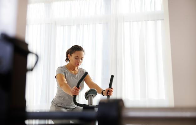 Молодая привлекательная подтянутая женщина сосредоточилась на кардио-тренировке дома
