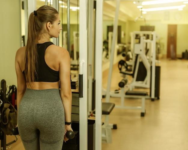 Молодая привлекательная женщина пригонки тренирует трицепс на тренажере в тренажерном зале.