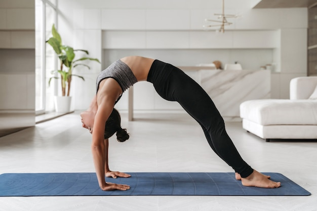 Young attractive fit woman practicing yoga at home in living room, stretching in urdhva dhanurasana exercise