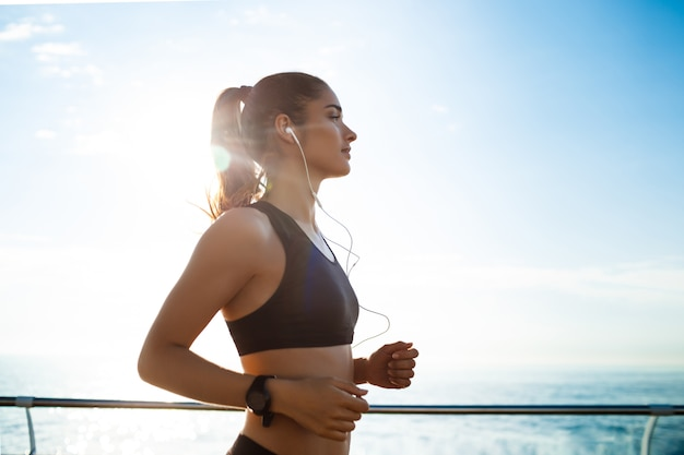 Young attractive fitness girl jogging with sea
