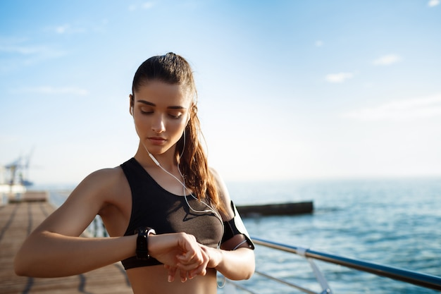Young attractive fitness girl looking at watch with sea coast on wall