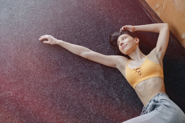 Young attractive fitness girl lying on the floor near the window on the background of a wooden wall